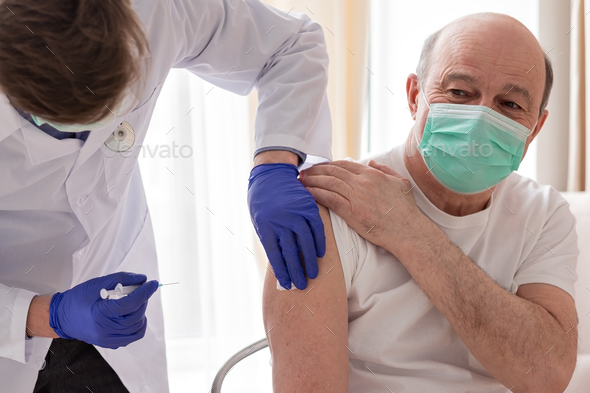 Doctor vaccinating senior male patient at home. - Stock Photo - Images