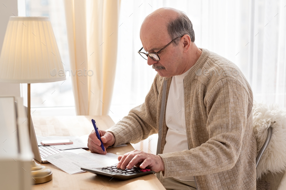 Senior man sitting with paperwork and using calculator while counting money - Stock Photo - Images