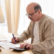 Senior man sitting with paperwork and using calculator while counting money - PhotoDune Item for Sale