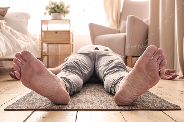 Caucasian man meditating on a wooden floor and lying in Shavasana pose - Stock Photo - Images