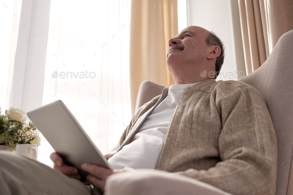 Senior man websurfing on internet with digital tablet sitting at home - Stock Photo - Images