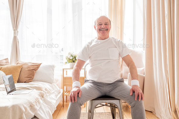 Elderly man wearing sport clothing sitting on chair ready for online yoga lesson - Stock Photo - Images