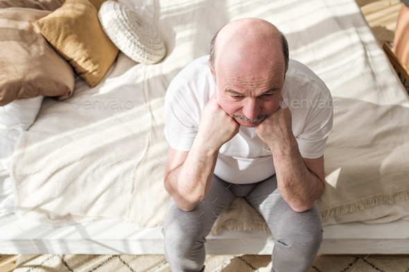 Sad caucasian man sitting on his bed with his head on his hand - Stock Photo - Images