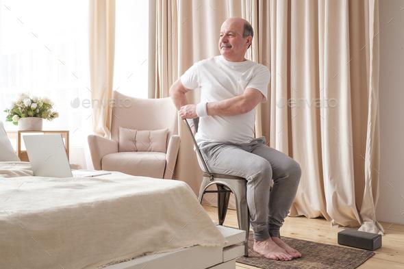 Sporty senior man practicing yoga using chair, doing Parivrtta Utkatasana - Stock Photo - Images