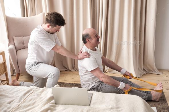 Male yoga trainer helps to senior man to do asana correctly. - Stock Photo - Images