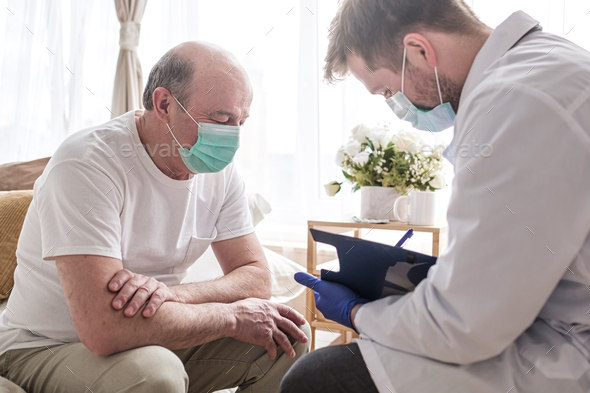 Doctor writing medical prescription to elderly man - Stock Photo - Images