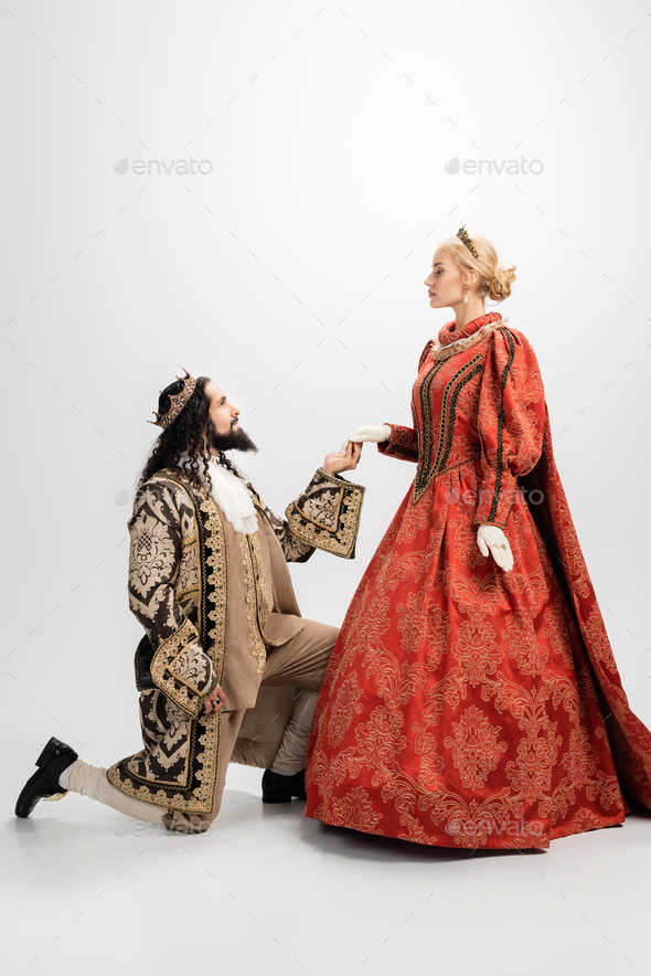 king in crown and medieval clothing standing on knee - Stock Photo - Images
