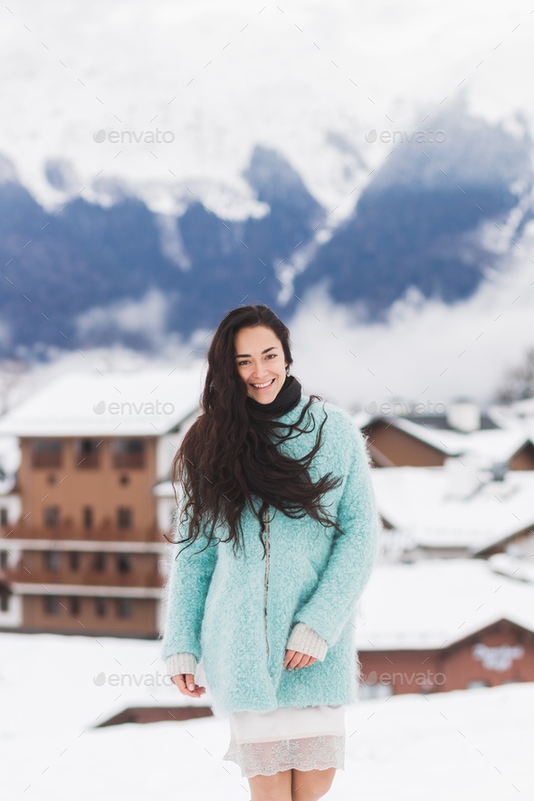 Happy girl is photographed in the mountains ski resort in the snow. Wearing aqua color coat - Stock Photo - Images