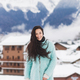 Happy girl is photographed in the mountains ski resort in the snow. Wearing aqua color coat - PhotoDune Item for Sale