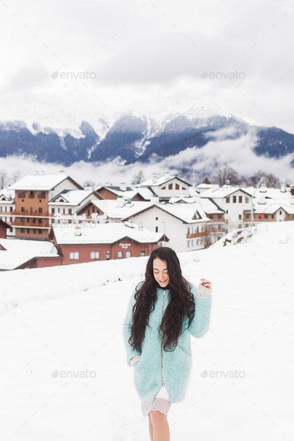 Happy girl is photographed in the mountains ski resort in the snow. Mountain village - Stock Photo - Images