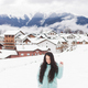 Happy girl is photographed in the mountains ski resort in the snow. Mountain village - PhotoDune Item for Sale