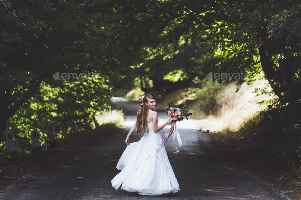 Portrait of happy bride on country road at summer. Wedding bouquet with silk ribbons. She whirls - Stock Photo - Images