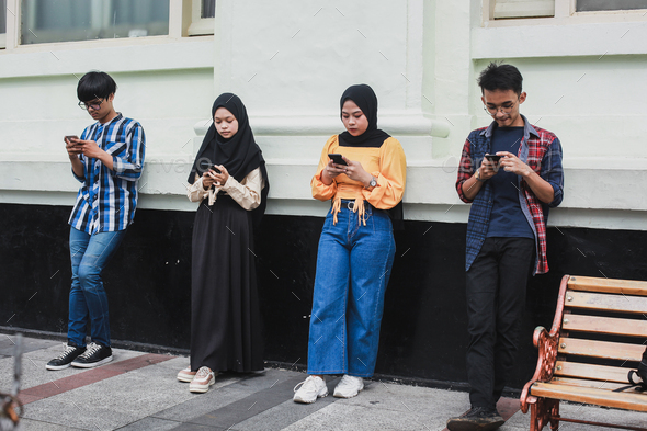 Group of people standing with distance and using smartphone together - Stock Photo - Images