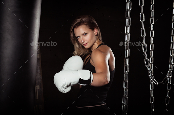 Sporting blonde woman in boxing gloves in dark studio looking at camera. - Stock Photo - Images