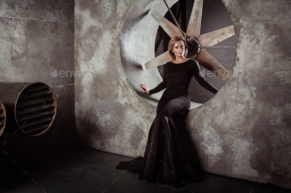 Pretty model sitting in sexy dress at grange studio - Stock Photo - Images