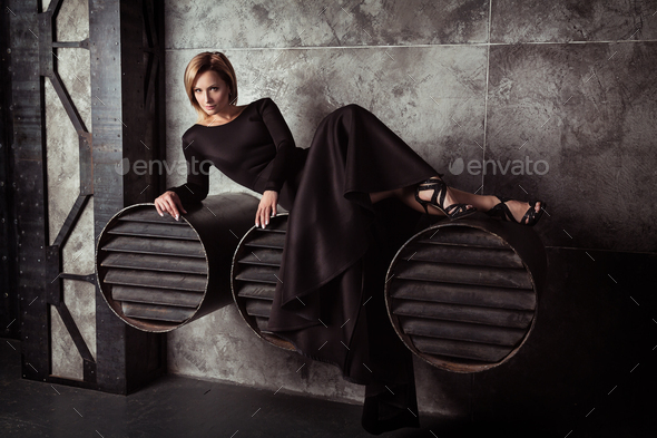 Beautiful model posing in sexy dress at black studio - Stock Photo - Images