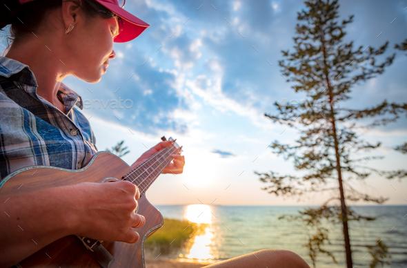 Woman at sunset playing the ukulele - Stock Photo - Images