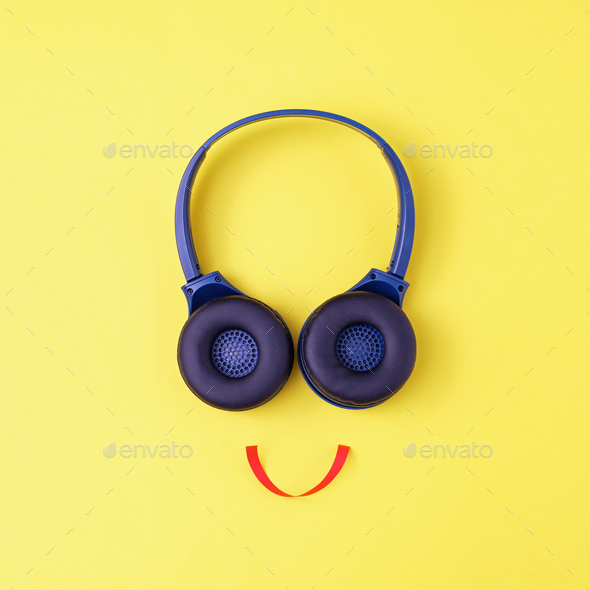 Headphones on a yellow background in the form of a happy face with a smile - Stock Photo - Images