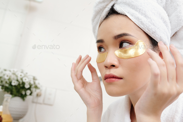 Woman applying undereye patches - Stock Photo - Images