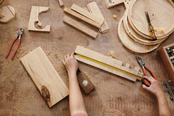 Carpenter measuring wooden details - Stock Photo - Images