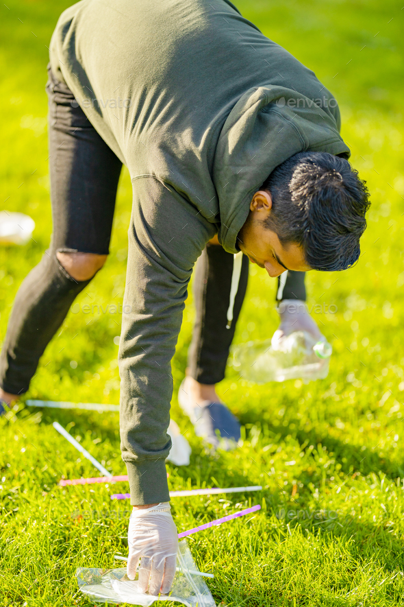 Volunteer cleaning park for garbage and plastic on sunny day - Stock Photo - Images