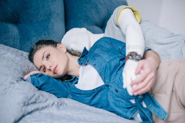 pensive woman lying on bed with mannequin behind, one way love concept - Stock Photo - Images