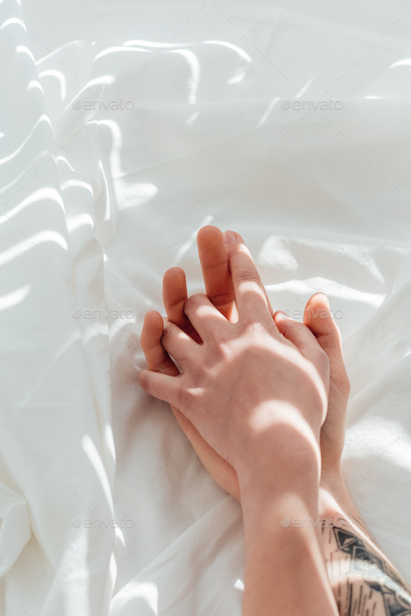 partial view of loving couple holding hands while lying on white bed sheet - Stock Photo - Images