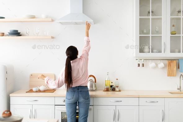 Woman select mode on cooking hood in kitchen - Stock Photo - Images