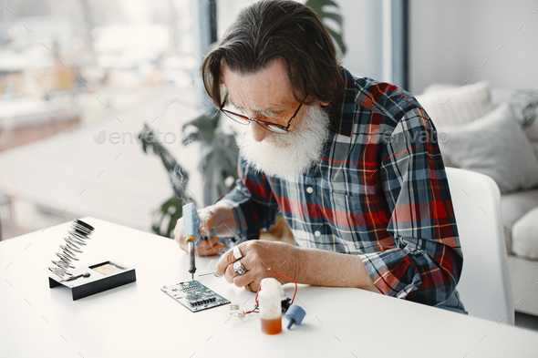 Male tech repairs electronic equipment at home - Stock Photo - Images