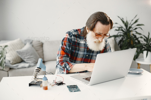 Senior man working with laptop in living room - Stock Photo - Images