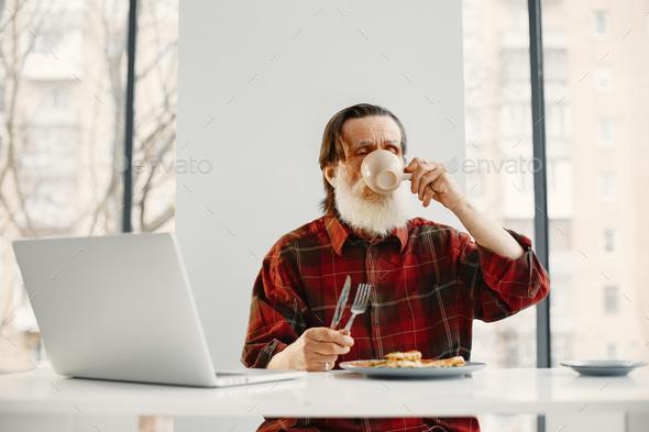 Senior man sitting in kitchen eating dinner - Stock Photo - Images