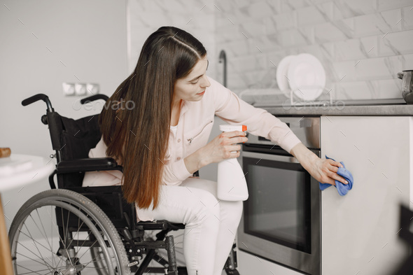 Young Handicapped Woman On Wheelchair Cleaning Stove - Stock Photo - Images