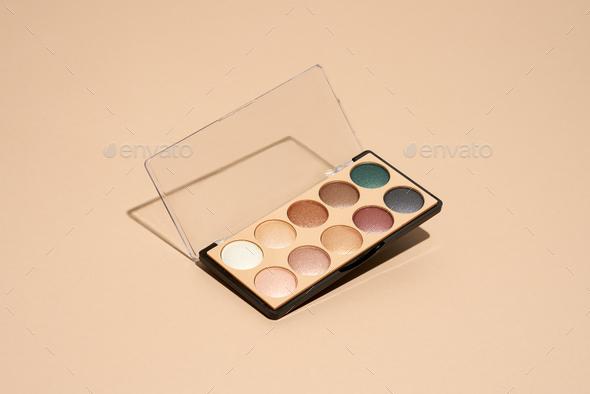 Make-up palette floating over a beige background - Stock Photo - Images