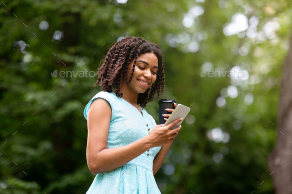 Happy black lady with coffee to go browsing internet on mobile phone at summer park - Stock Photo - Images