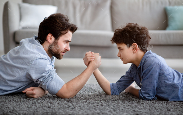 Raising a real man. Concentrated father and son arm wrestling and competing while lying on floor - Stock Photo - Images