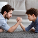 Raising a real man. Concentrated father and son arm wrestling and competing while lying on floor - PhotoDune Item for Sale