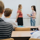 view of a large class full of students and a teacher are standing in front of the blackboard - PhotoDune Item for Sale
