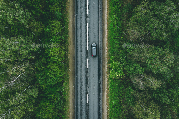 Aerial view of country road with car driving through green forest and corn fields - Stock Photo - Images