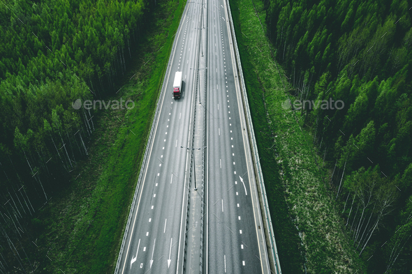 Aerial view of toll road highway with cars and trucks through green forest - Stock Photo - Images