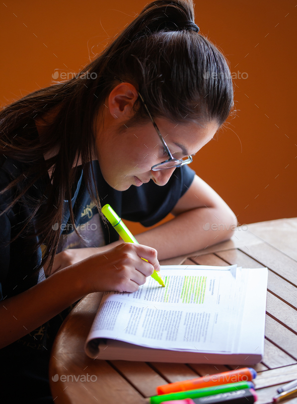 University student studying for an exam underlining text with highlighter. - Stock Photo - Images