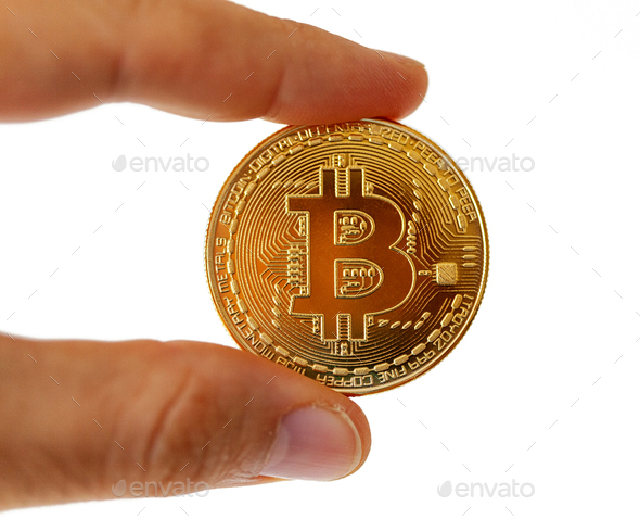 A Bitcoin coin between your fingers. Subject isolated on white background. - Stock Photo - Images