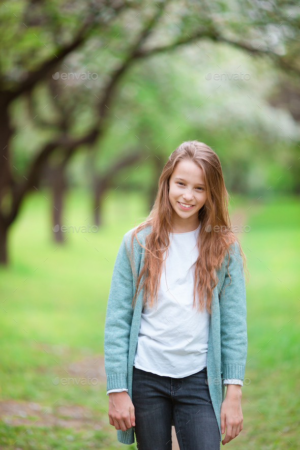 Little smiling girl playing in the park - Stock Photo - Images