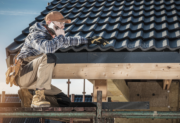 Roof Construction Worker Making Phone Call While Staying on Scaffolding. - Stock Photo - Images