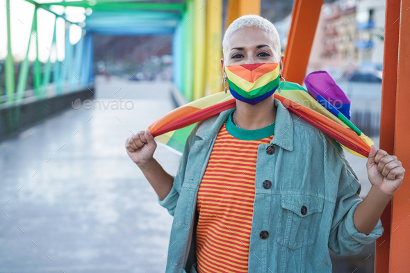 Young woman wearing LGBT rainbow flag during coronavirus outbreak - Focus on face - Stock Photo - Images