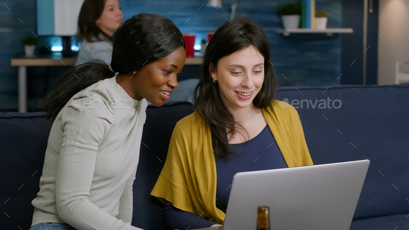 Mixed race women enjoying time spend together looking at movie on laptop - Stock Photo - Images