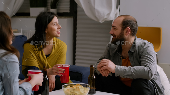 Multi-ethnic friends socializing during night home party while resting on couch - Stock Photo - Images