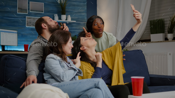 Excited group of multiracial friends sitting on sofa during joyful party - Stock Photo - Images