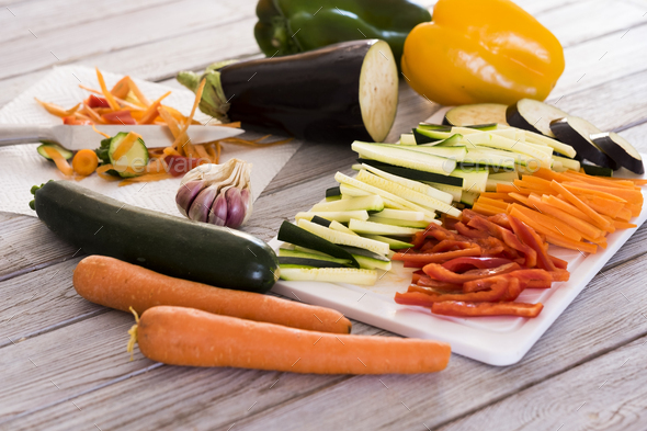 Fresh vegetables on a wooden table with a mix of sliced carrots, zucchini, eggplant and peppers - Stock Photo - Images