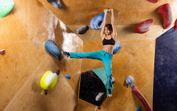 Caucasian young woman bouldering in indoor climbing gym - Stock Photo - Images
