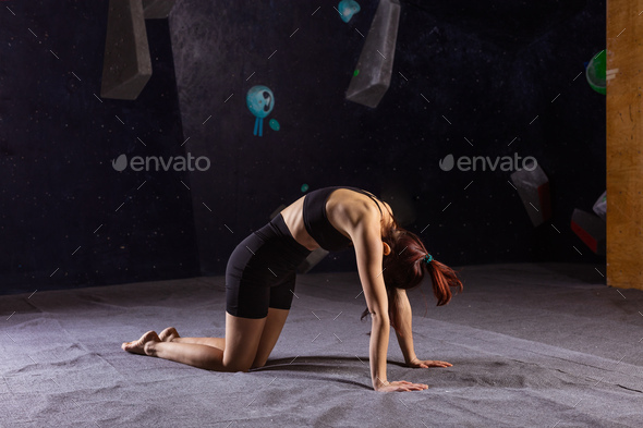 Athletic young woman practicing yoga Cat Cow pose in climbing gym - Stock Photo - Images